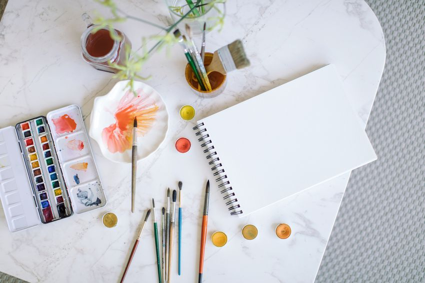 High Angle View Of Various Paintbrushes And Watercolor Paints With Spiral Notebook On Table