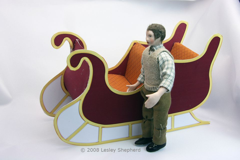 A teenage dolls house doll stands beside a printable miniature sleigh.