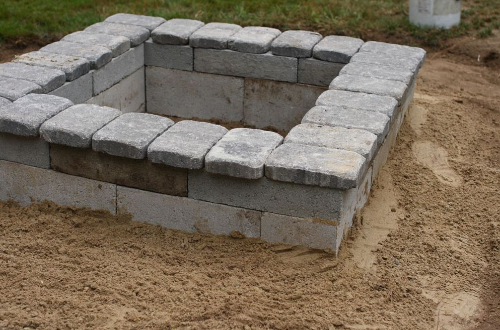 A square fire pit made out of concrete blocks