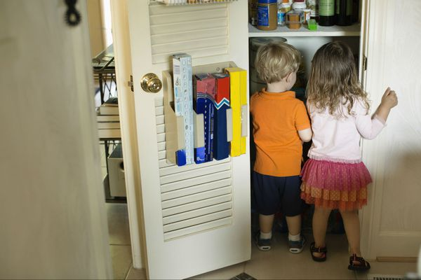 Male and female toddlers searching a pantry