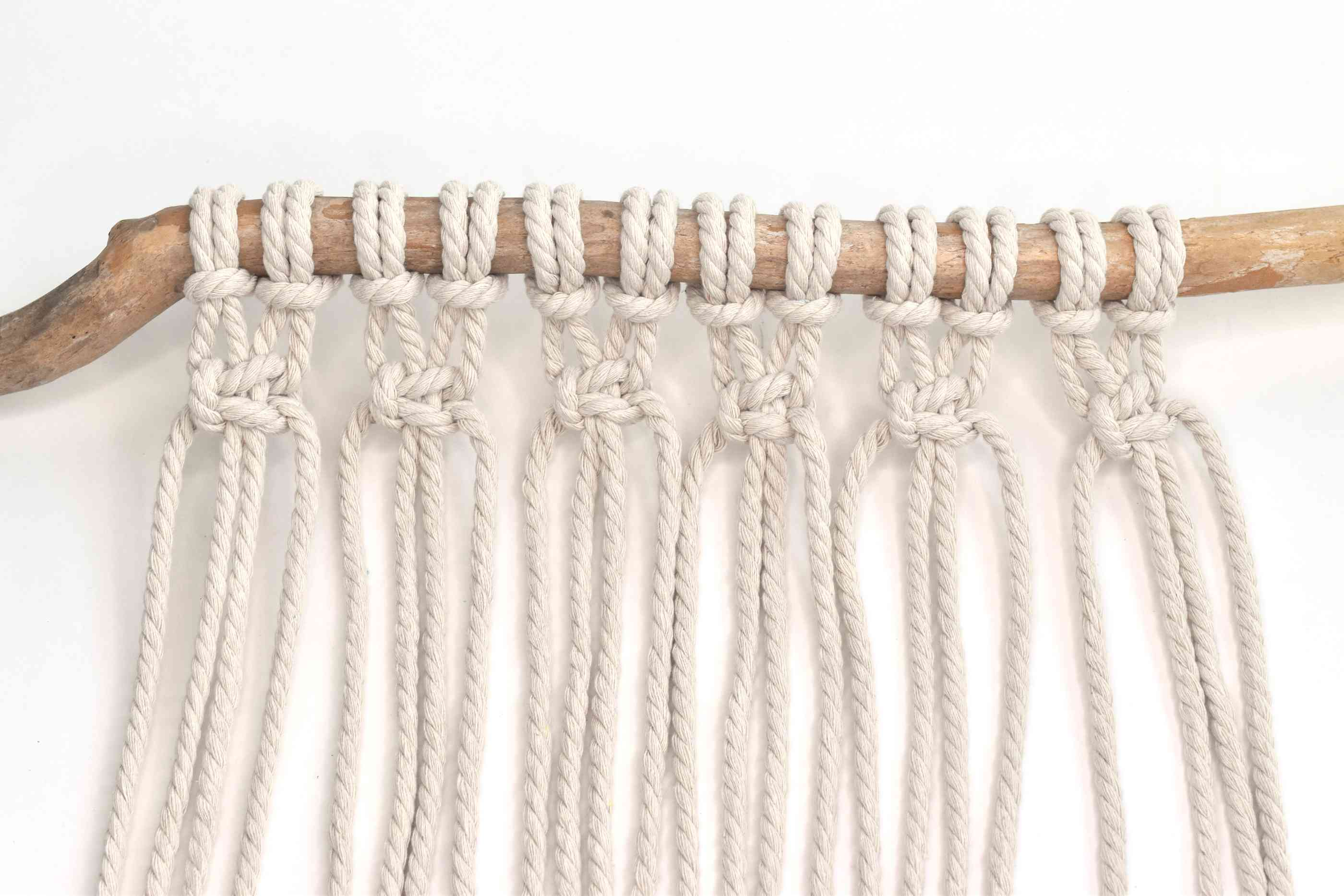 Tie left-facing square knots across all the ropes