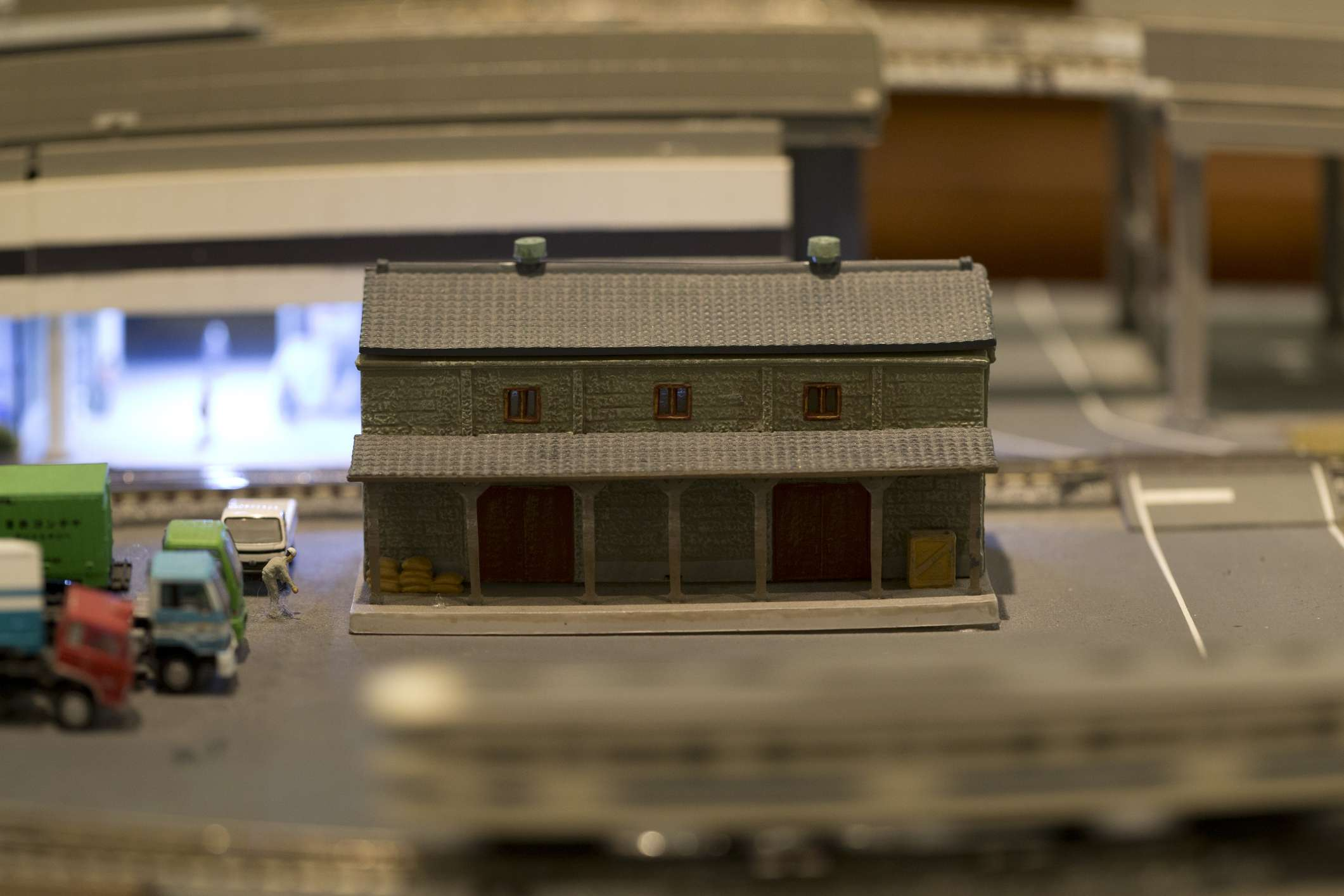 Miniature model building, with electric toy train whizzing by in the foreground.