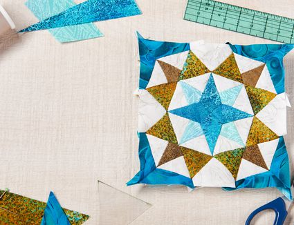 Patchwork block and sewing accessories on white wooden surface