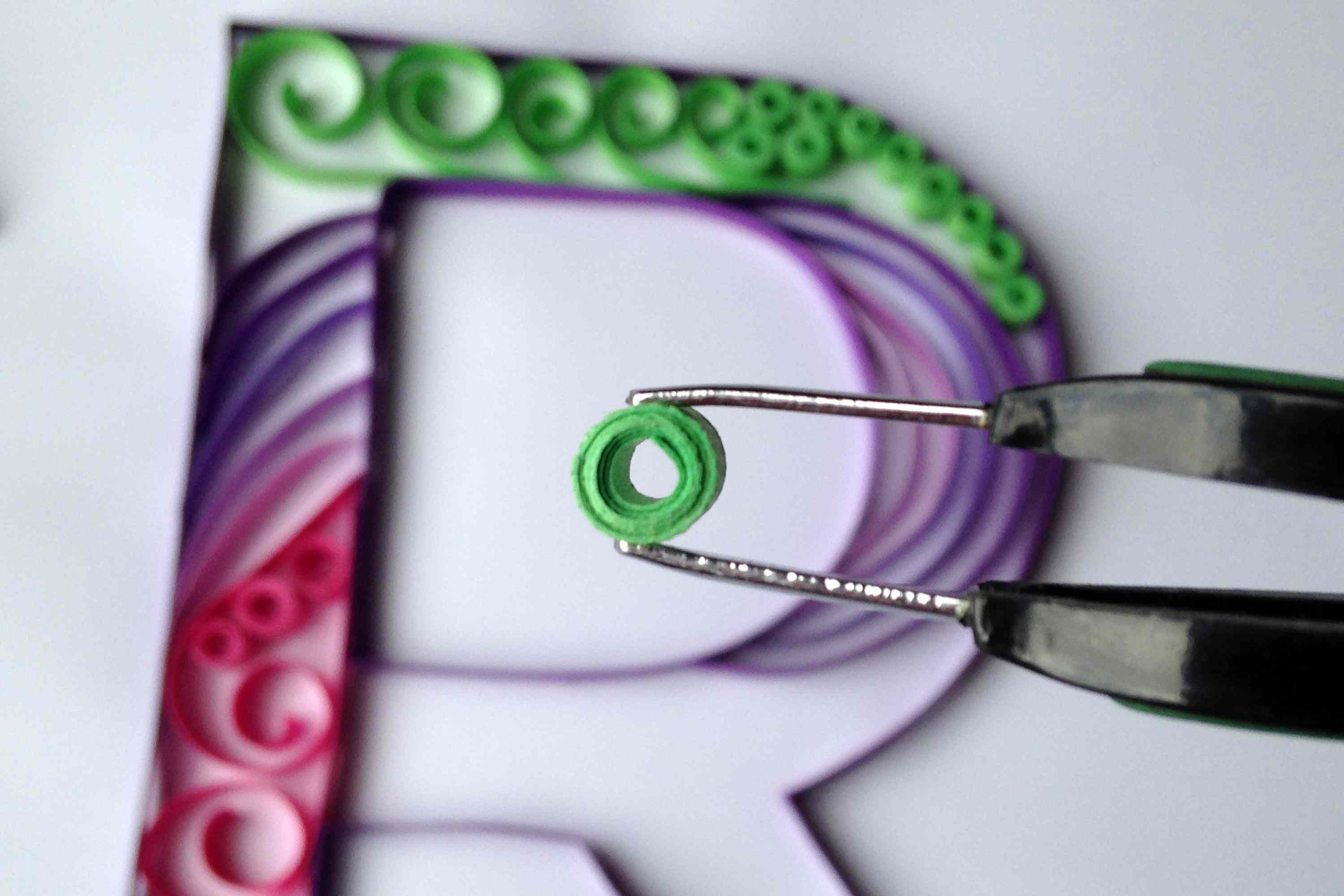 tweezers holding roll of quilled paper