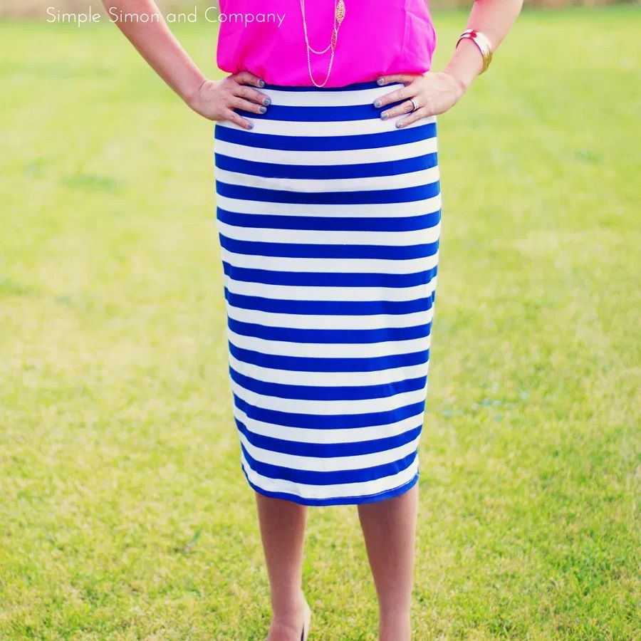 A woman wearing a pink shirt and blue and white striped skirt