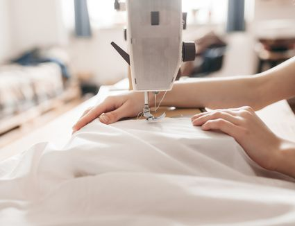 Close-up of fashion designer threading sewing machine
