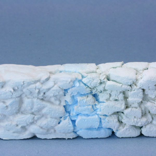 Paintable protective coatings over dense insulation foam carve to resemble a miniature stone wall.