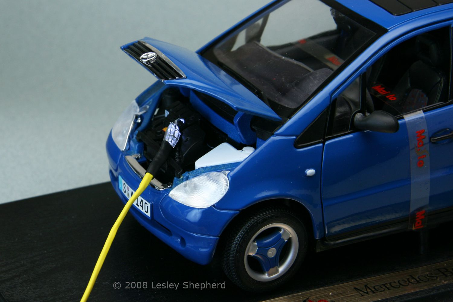 A die cast car engine lit up by a working model trouble light in 1:18 scale.