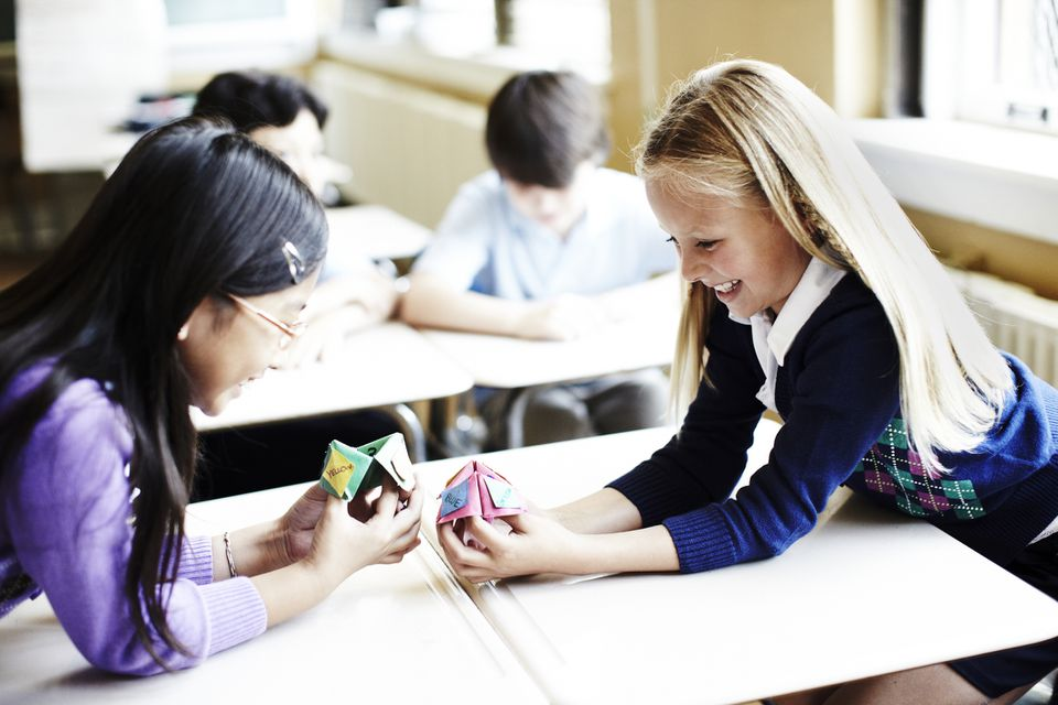 Two girls playing with a paper fortune teller