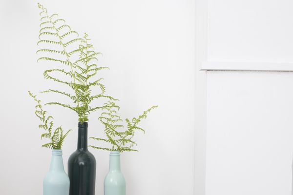 light and dark blue painted wine bottles with foliage in them