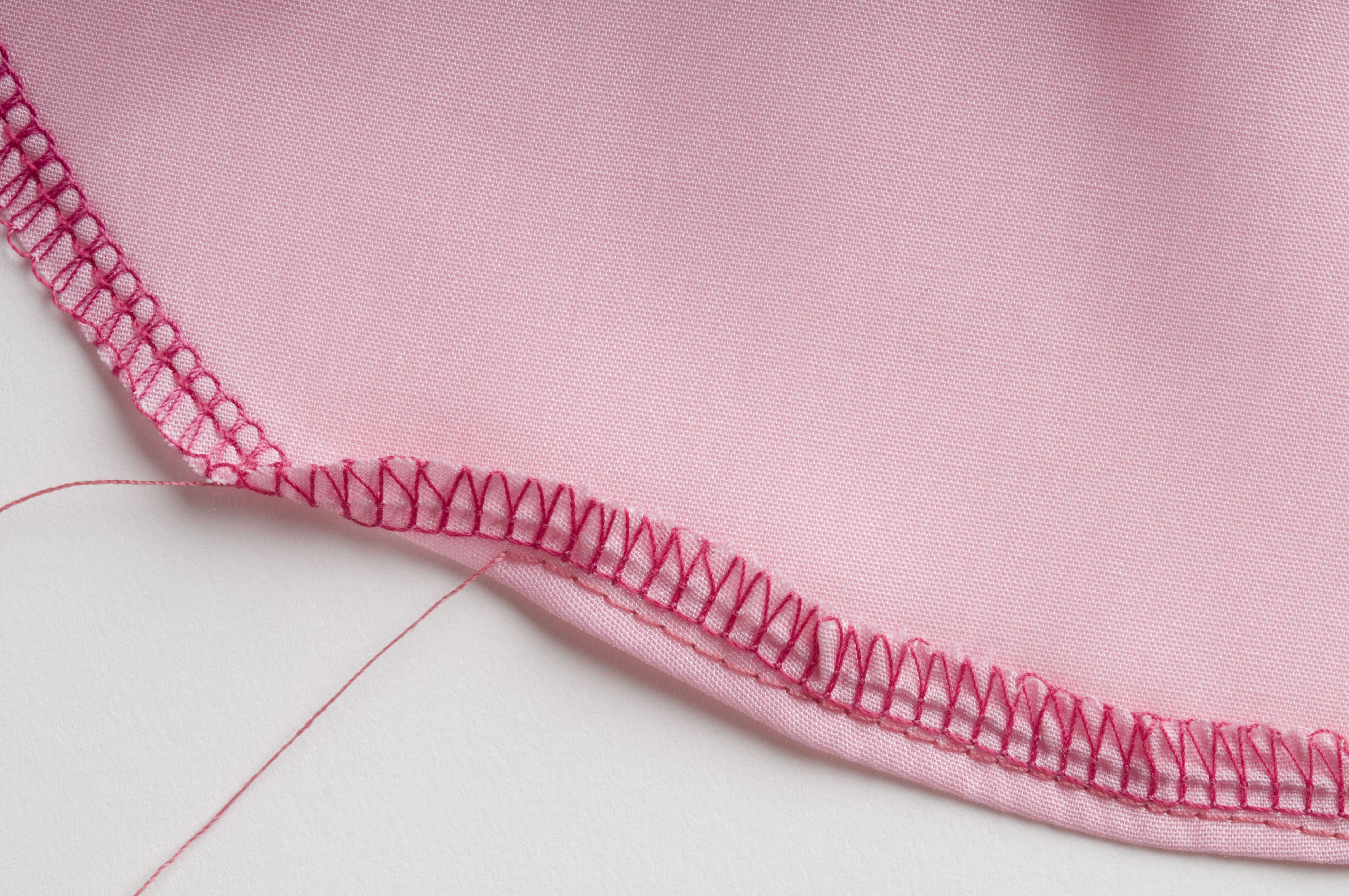 Overlock stitch and straight stitch along curved edge of pink fabric