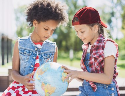 Happy little girls looking at globe
