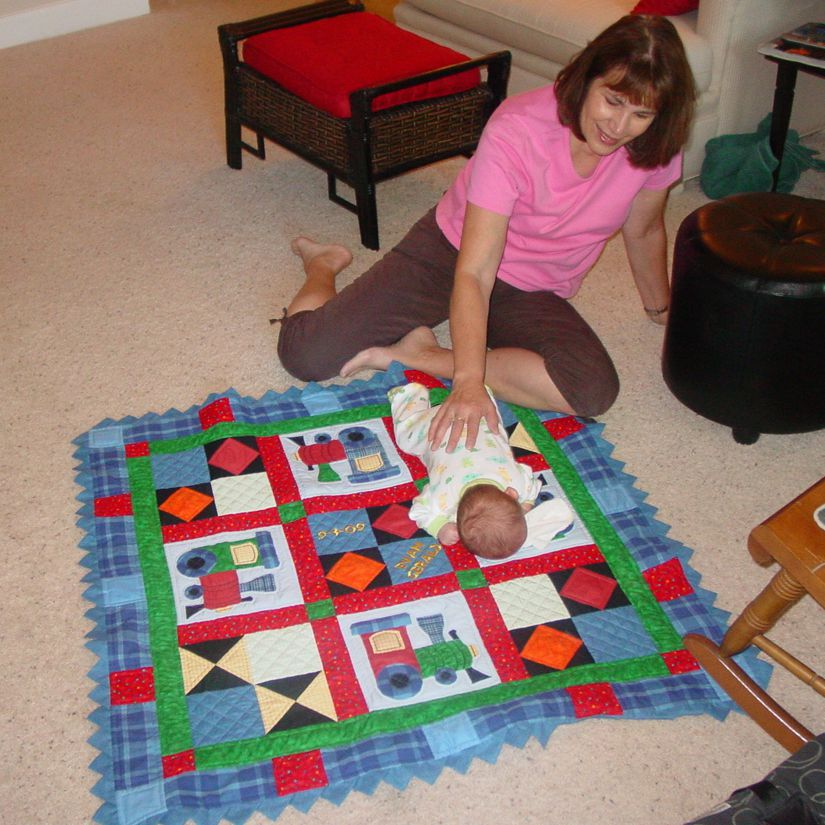 Grandma with baby on the floor with a train baby quilt.