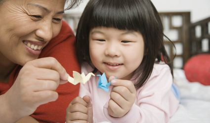 Woman and child holding origami cranes