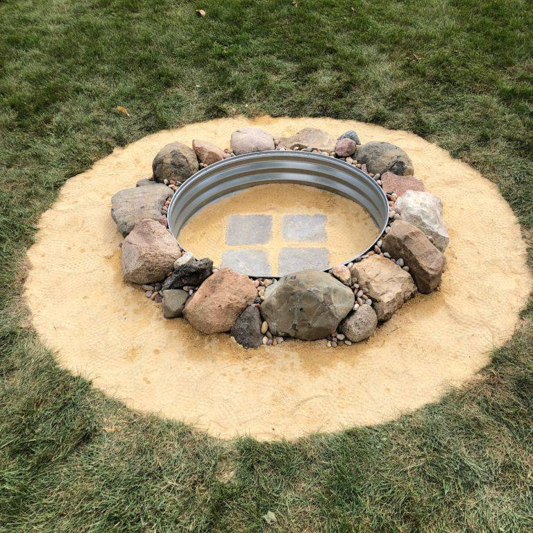 A fire pit surrounded by sand
