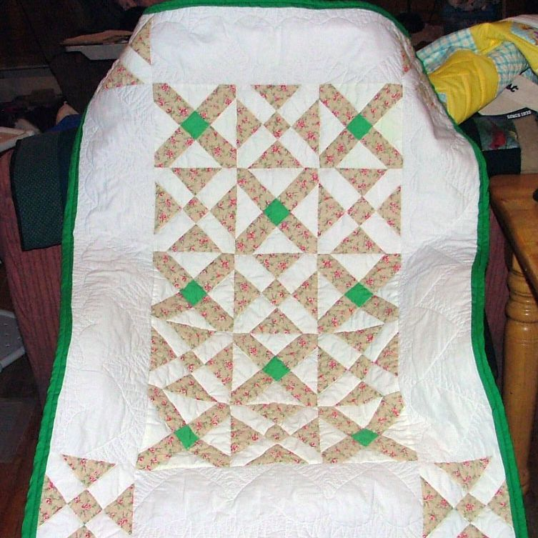 White baby quilt with green border.