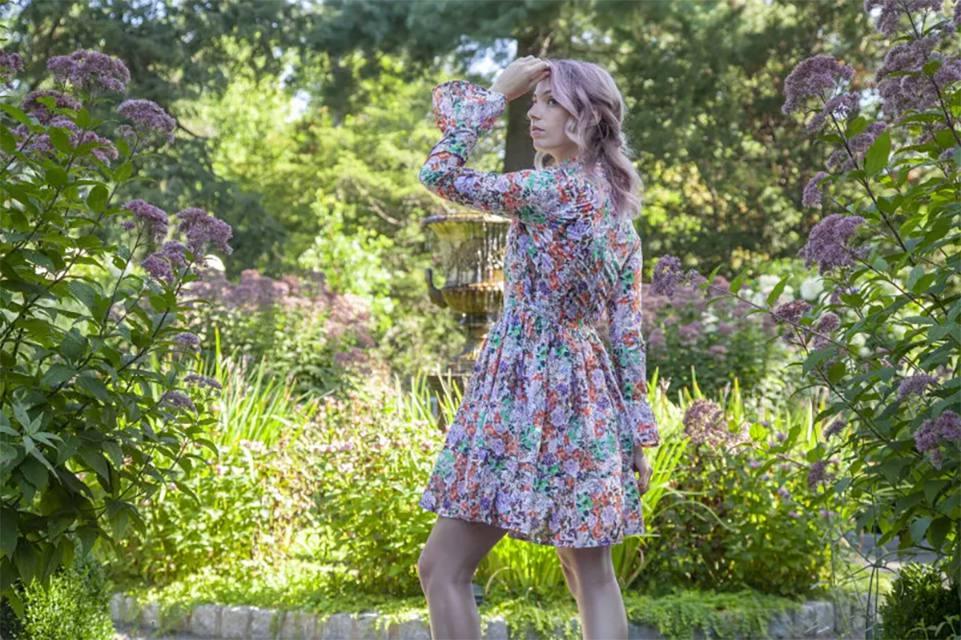 A woman wearing a sewn dress in a garden