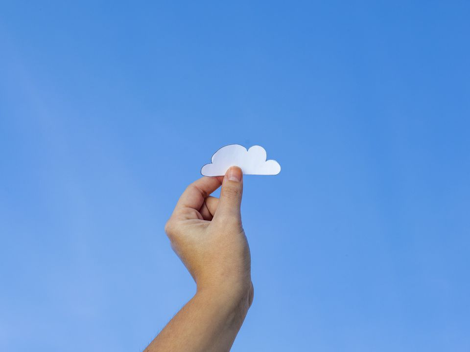 Hand holding up paper cloud to the clear sky