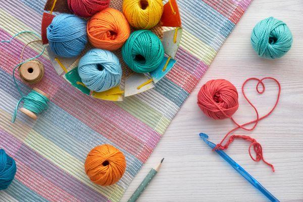 Crochet and yarn balls, top view on light wood