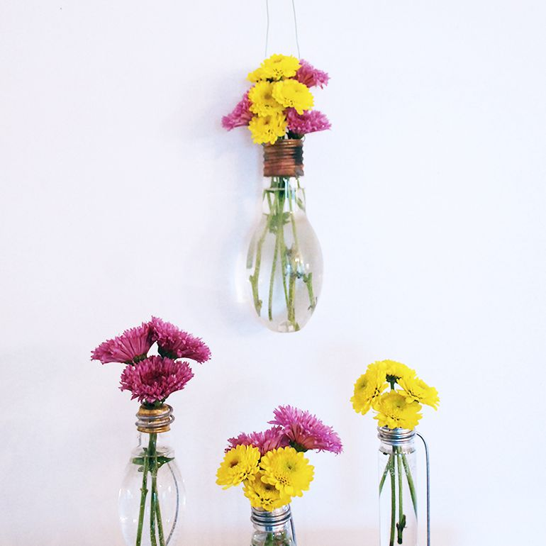 Vases made from light bulbs hanging and standing on a table with flowers.