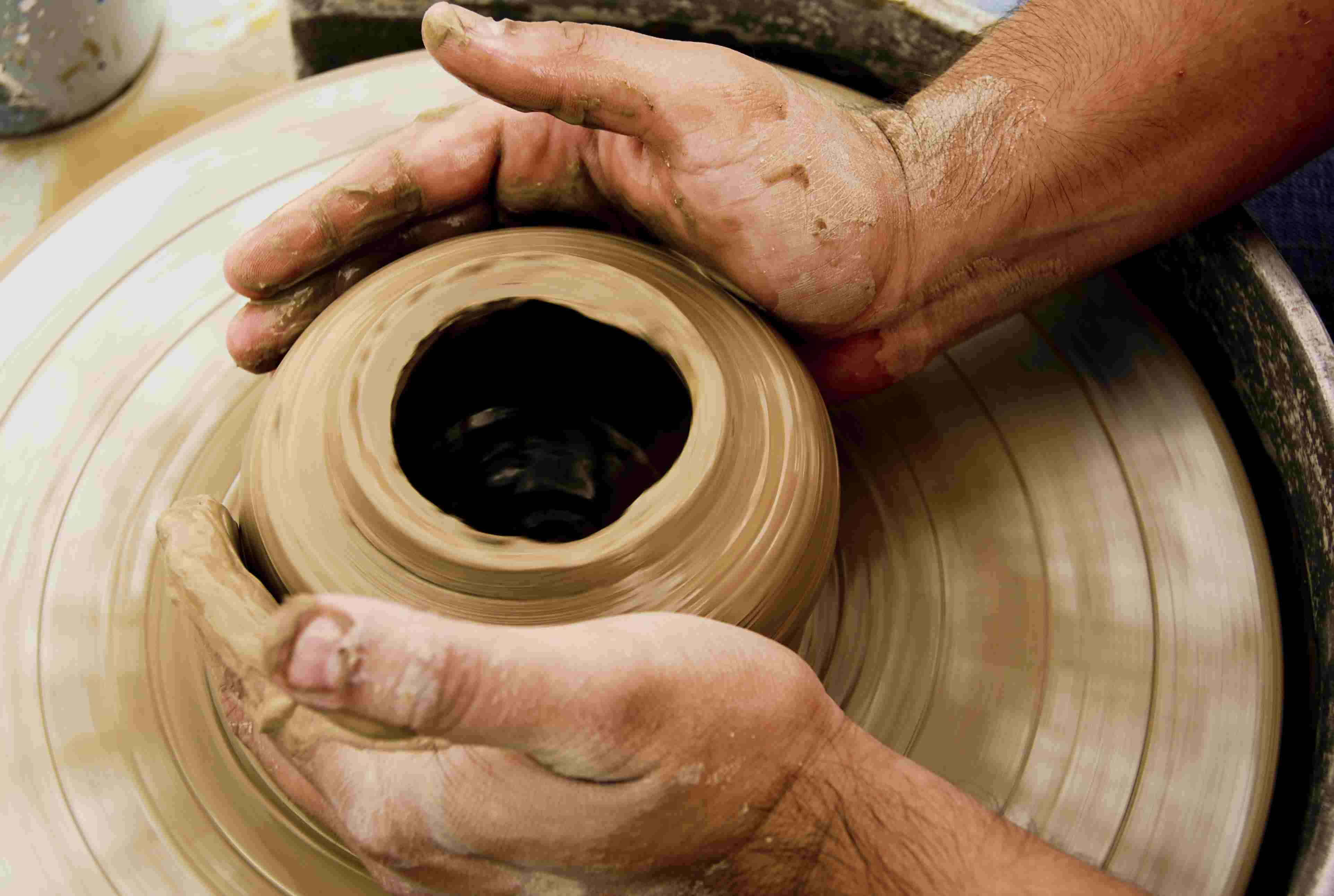 A man's hands at the potter's wheel