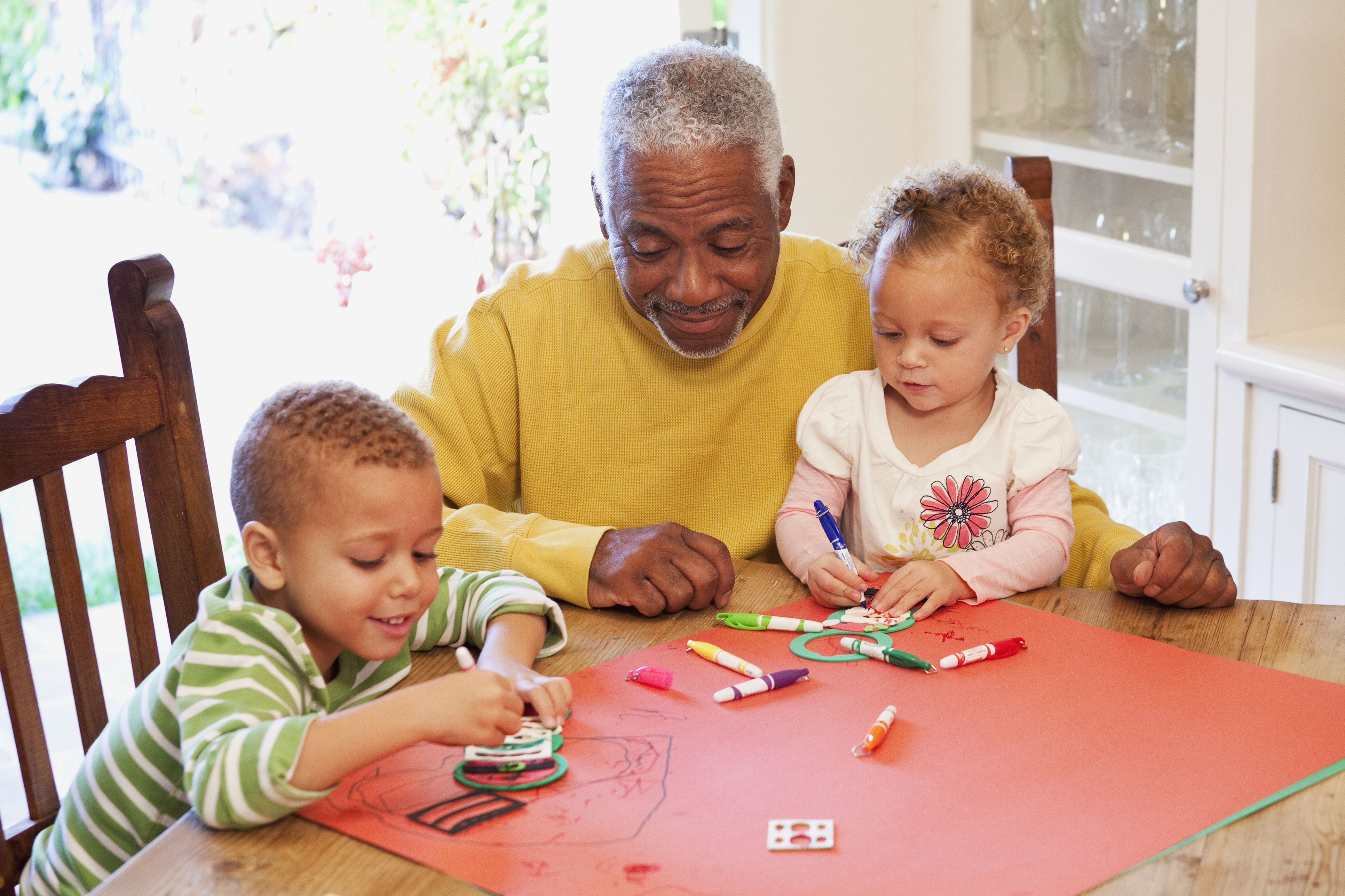African American man drawing with grandchildren
