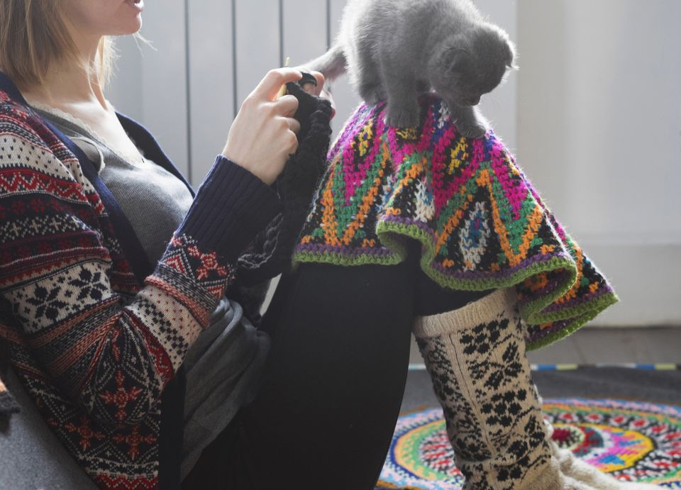 A woman crocheting a blanket with a cat