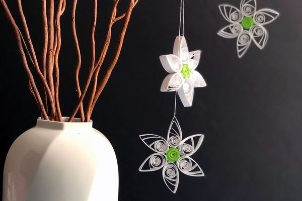 paper quilled daisies hanging next to a vase