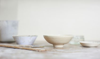 A potter's studio work table with hand crafted bowl and utensils.