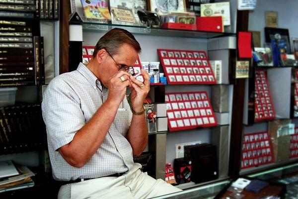 A coin dealer inspecting a coin in his coin shop.