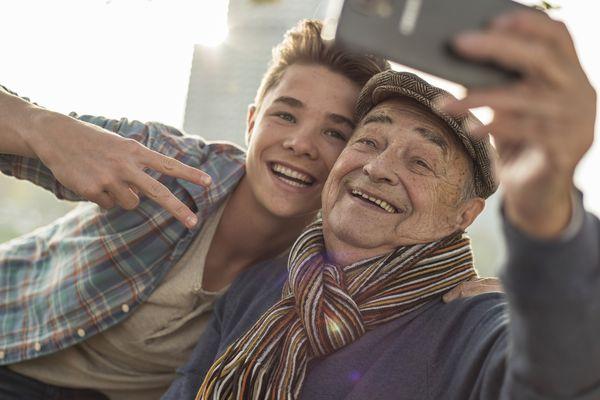Happy senior man taking a selfie with grandson