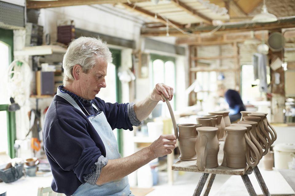 Potter putting handles on medium brown jugs