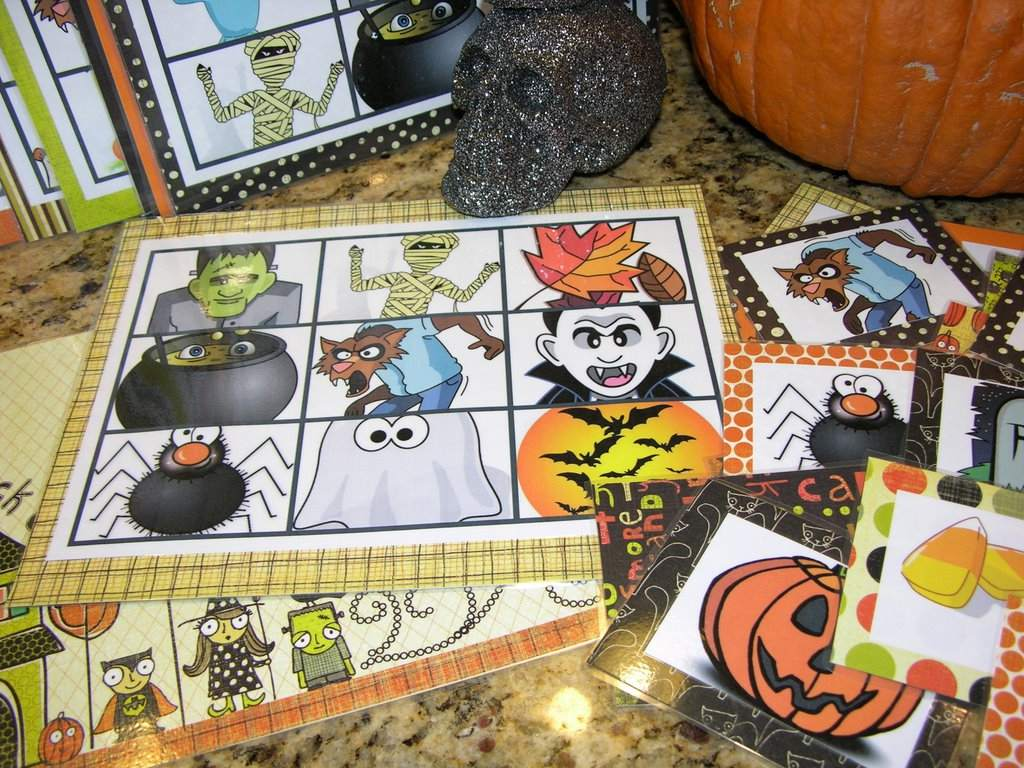 A Table With Halloween Bingo Cards, a Skull, and a Pumpkin on It