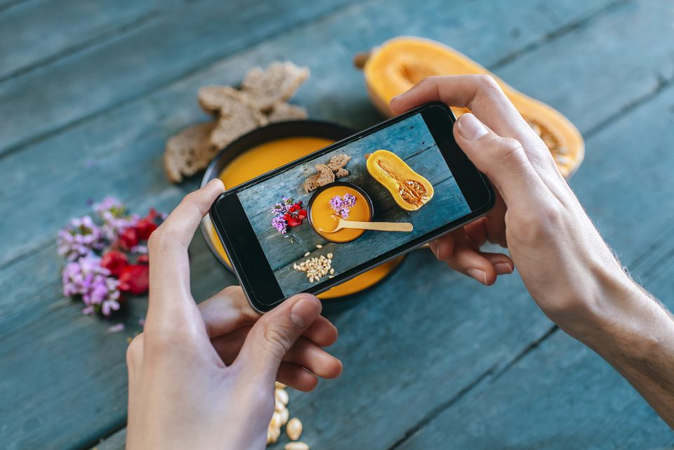 Close-up of mans hands taking picture of creamed pumpkin soup with smartphone