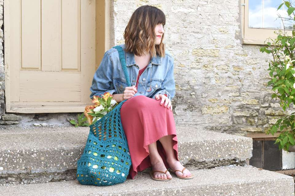 Woman Sitting on Steps With Filled DIY Crochet Market Bag