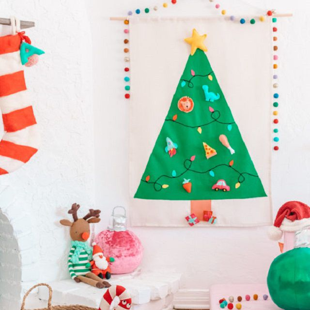 A felt Christmas tree hanging on the wall next to kids toys.