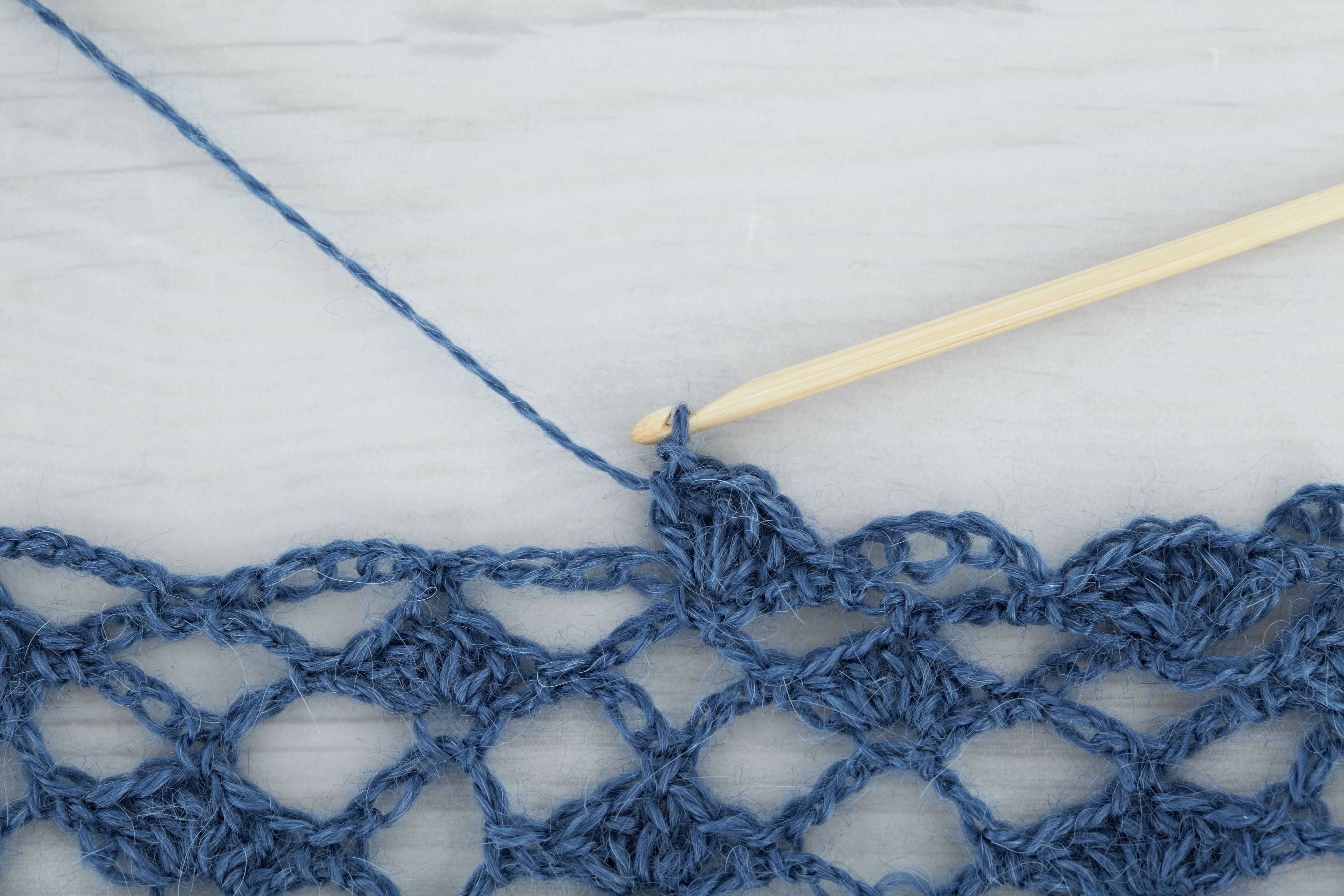Crochet hook with blue wool making openwork scarf