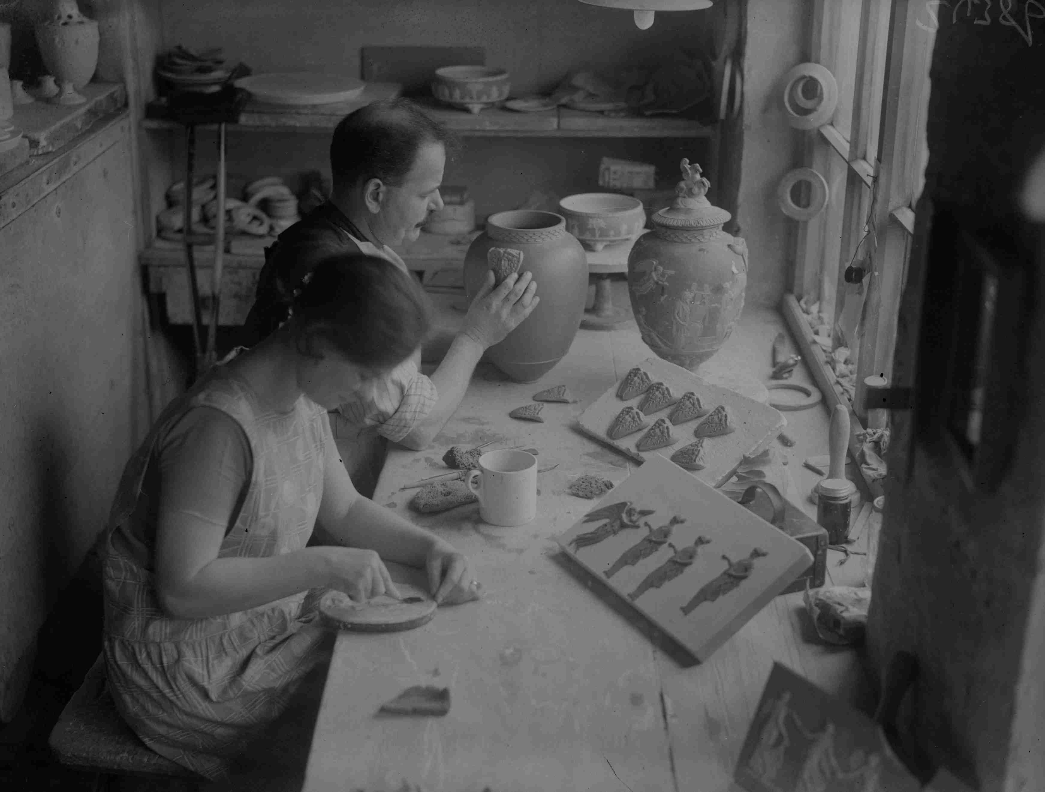 Two technicians applying relief moulding to pots in a workshop at the Wedgwood pottery, Stoke-On-Trent, Staffordshire.