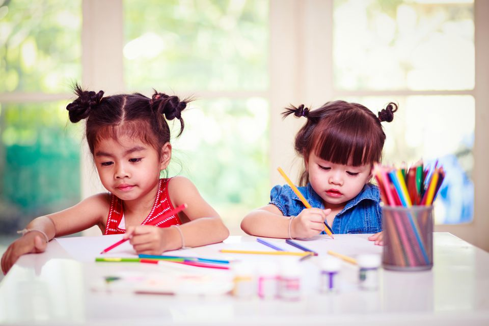 Little girl drawing together in white room with window. Children doing homework.