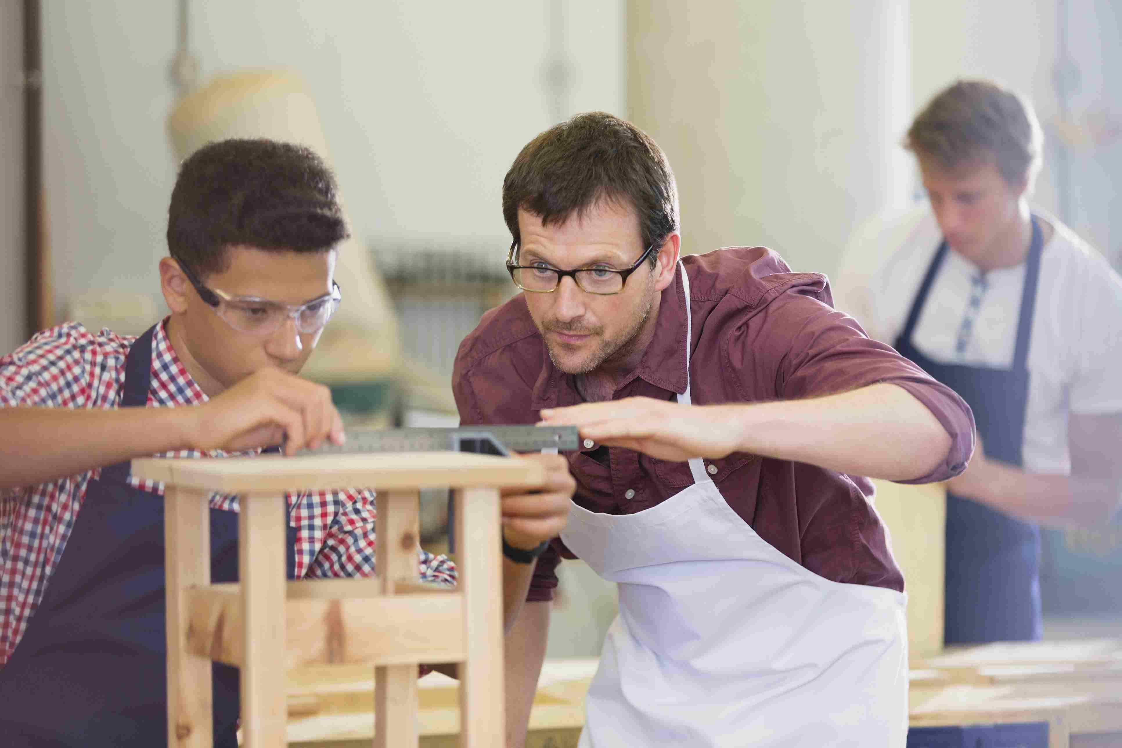 Focused carpenters measuring wood in workshop