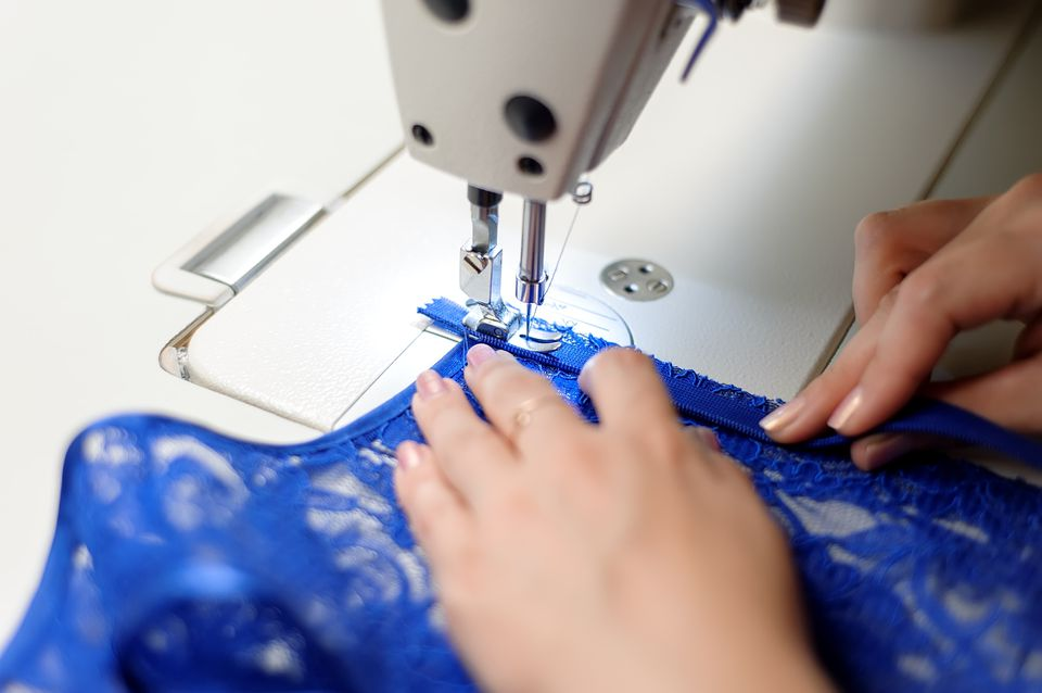 Woman stitching fabric on sewing machine
