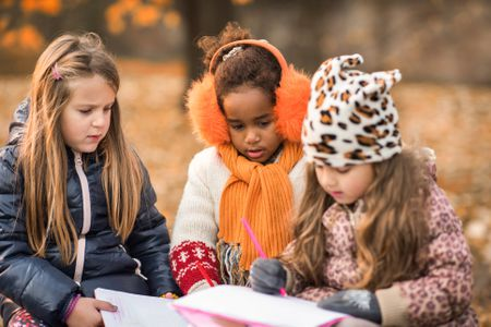 Cute Little Girls Drawing In Notebooks At The Park