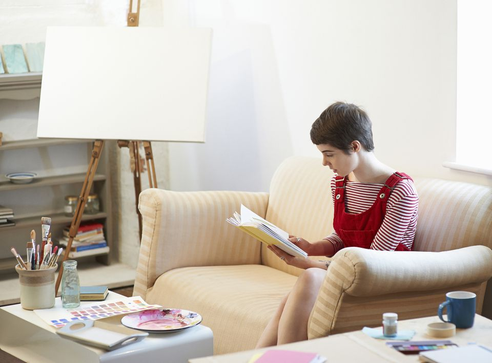 Female artist reading near her paint and canvas