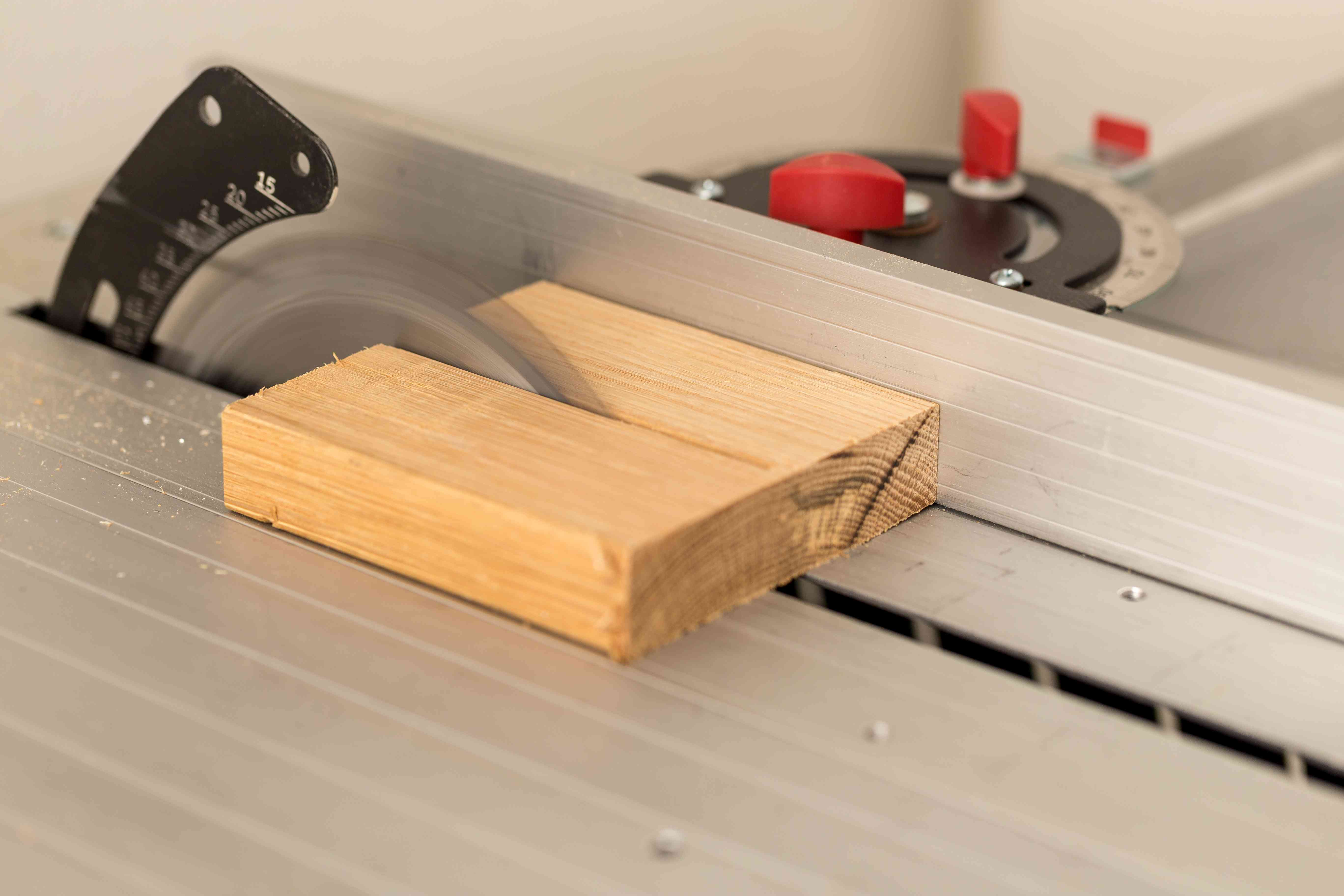 Close-Up Of Wood Being Cut With Circular Saw On Table