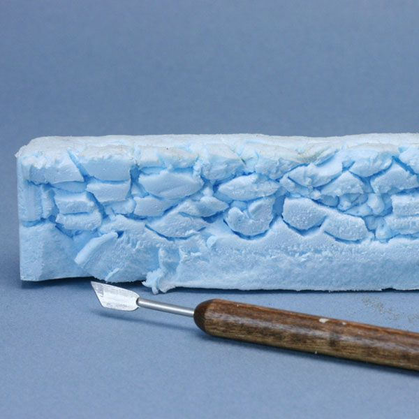 Stone shapes carved into dense insulation foam to create a scale model stone wall from foam.