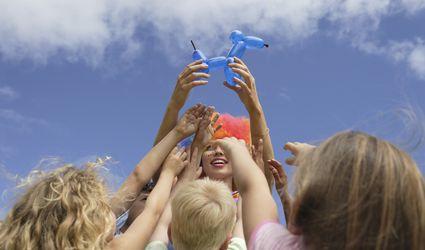 Children reaching for balloon sculpture