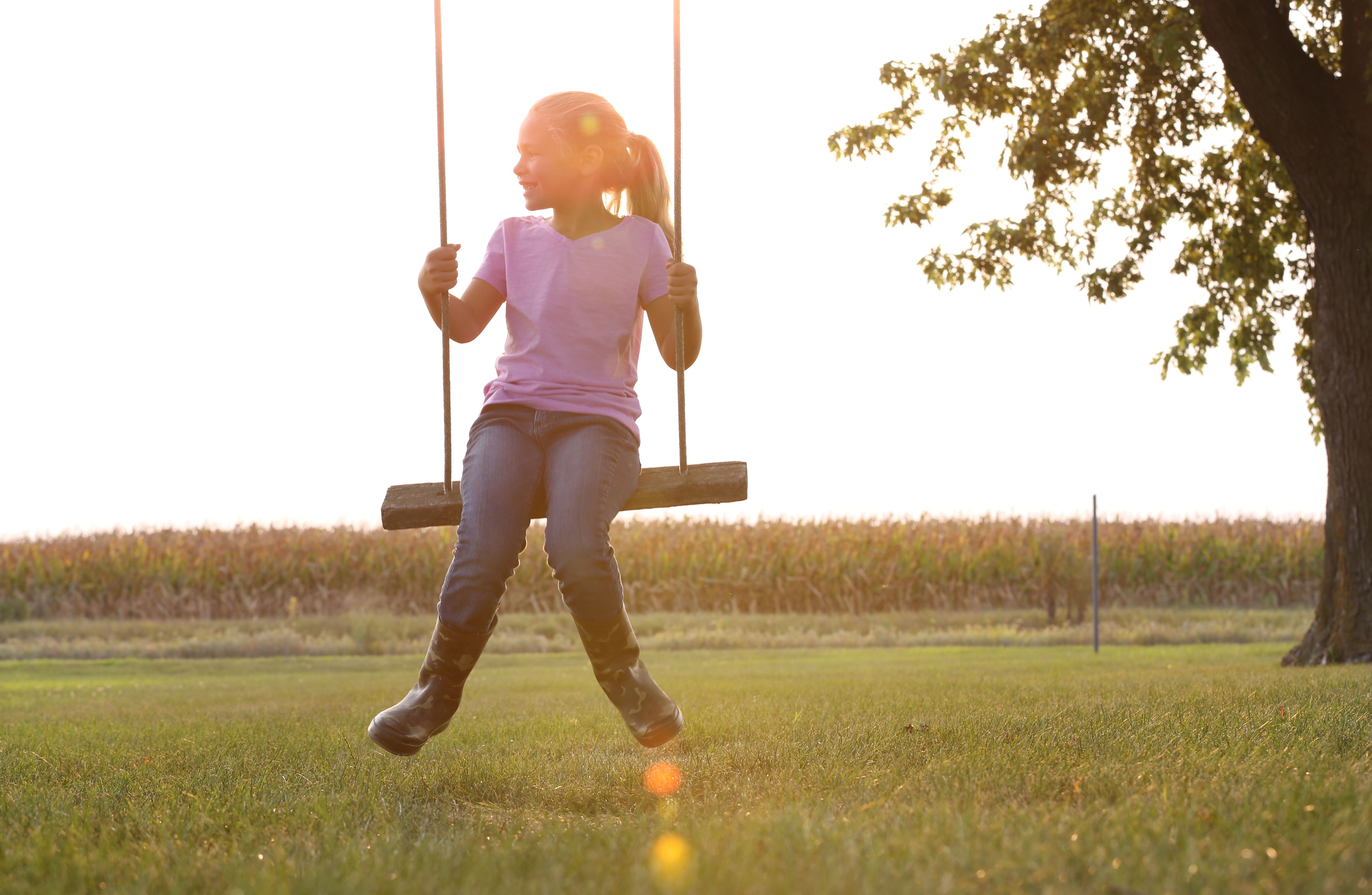 Young girl on wooden swing