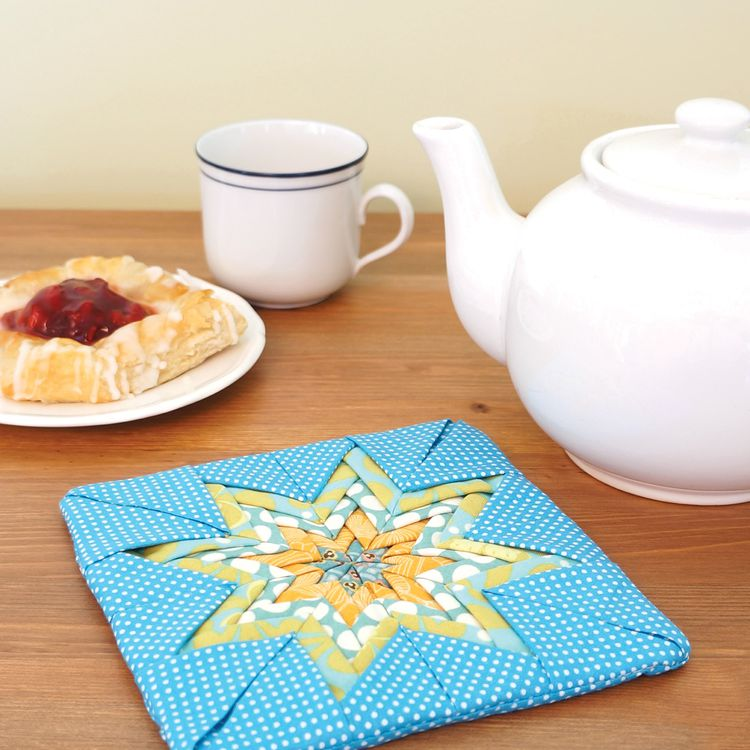 A yellow and blue folded star pot holder with a tea kettle and danish beside it