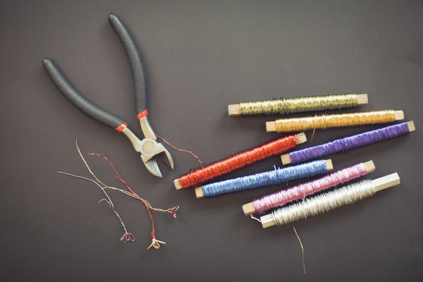 Pliers and seven colorful wire spools on table.