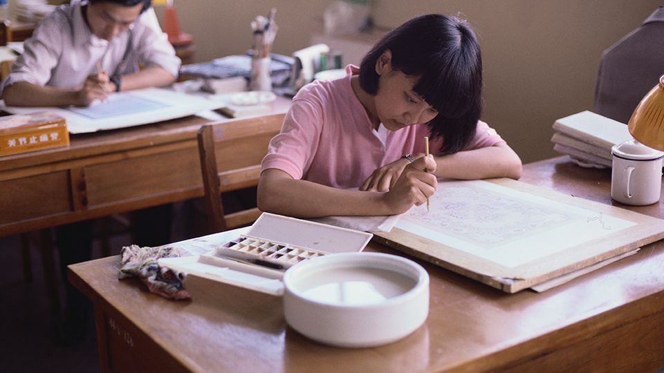 A woman designing a stencil for her ceramics
